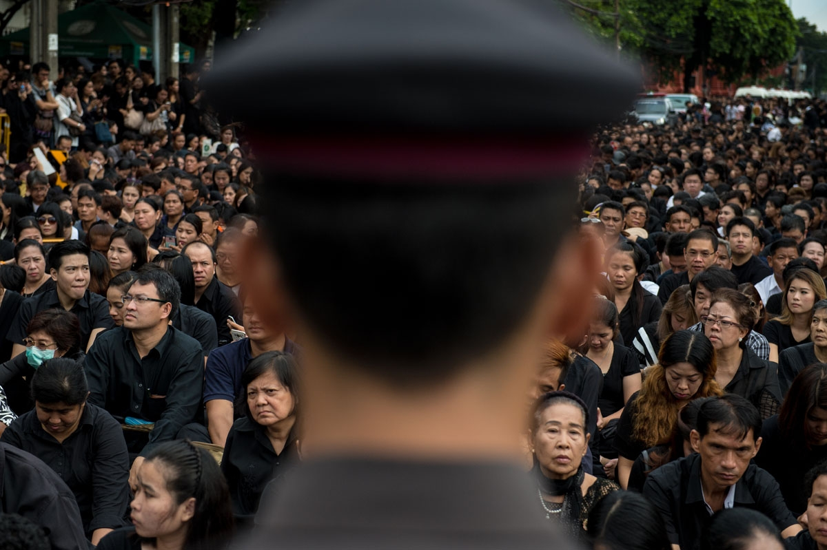 A large crowd clad in black who came to pray for the late Thai King Bhumibol Adulyadej is watched by a Thai policeman in front of the Grand Palace in Bangkok on October 16, 2016.