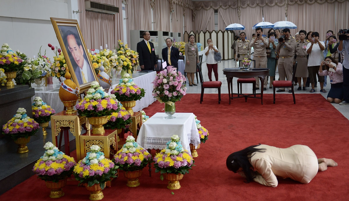 Ousted Thai prime minister Yingluck Shinawatra bows to a portrait of Thai King Bhumibol Adulyadej as she pays her respects during a visit at the Siriraj hospital in Bangkok on October 6, 2014. Thailand's revered 86-year-old King Bhumibol Adulyadej has had