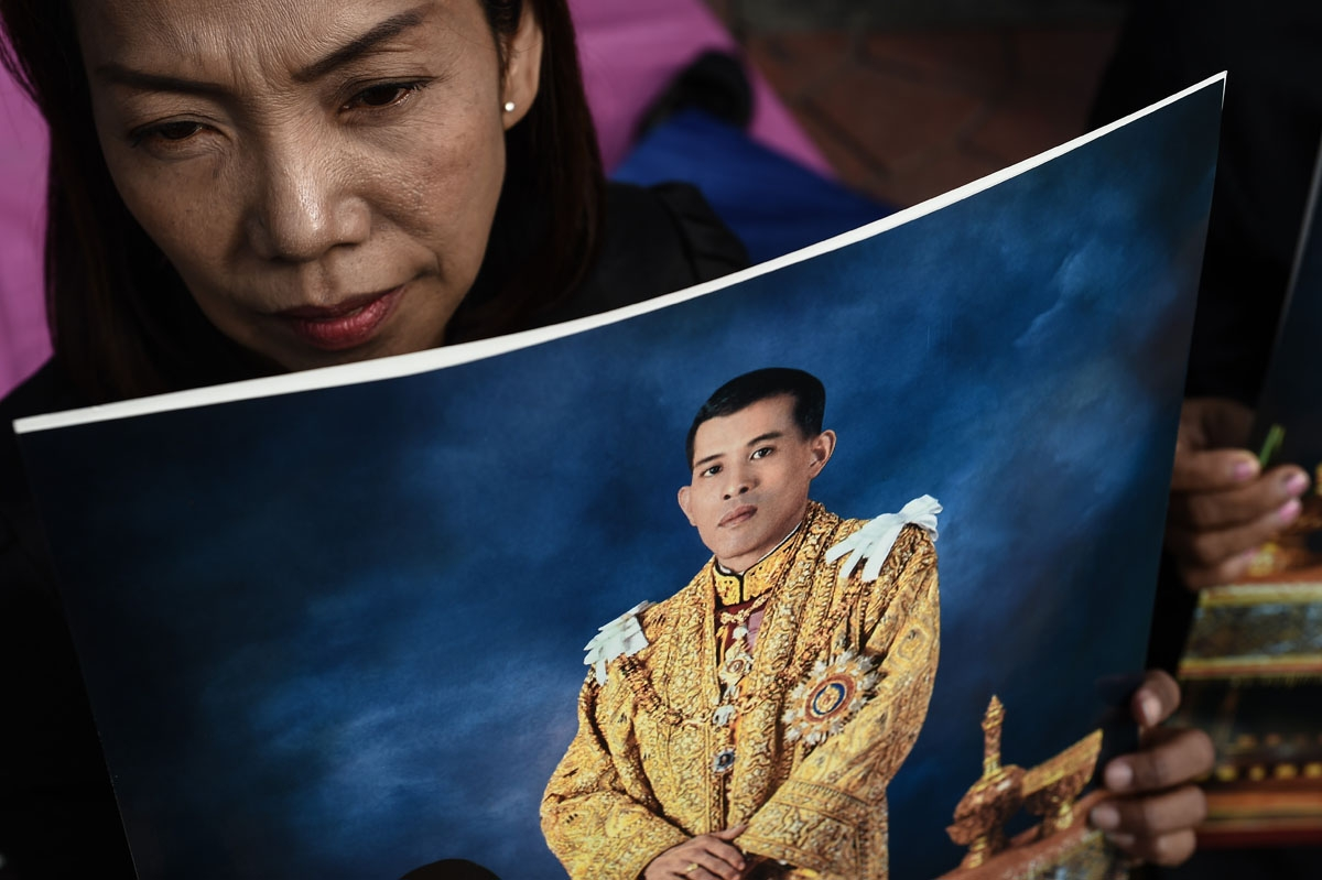 A woman holds an image of Thailand's new King Maha Vajiralongkorn outside the Grand Palace in Bangkok on December 2, 2016.