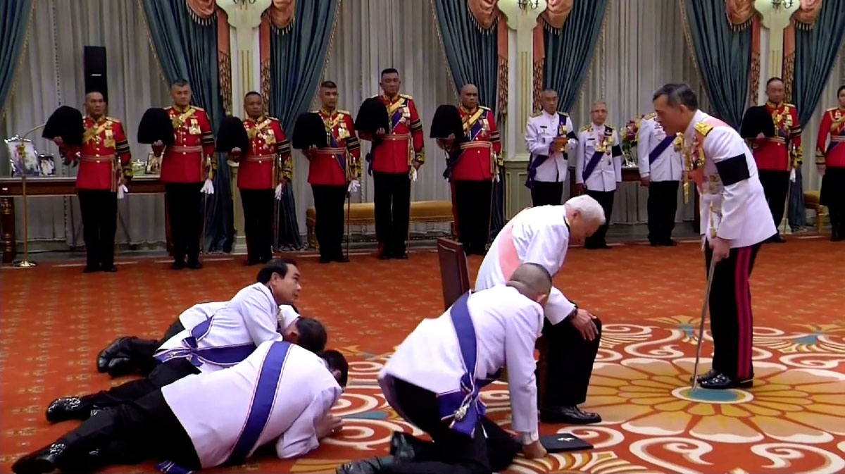 This screengrab from Thai TV Pool taken on December 1, 2016 shows Thai Prime Minister Prayuth Chan-Ocha (middle L) and Privy Council President General Prem Tinsulanonda (C, pink sash) prostrating themselves in front of newly appointed Thai King Maha Vajir