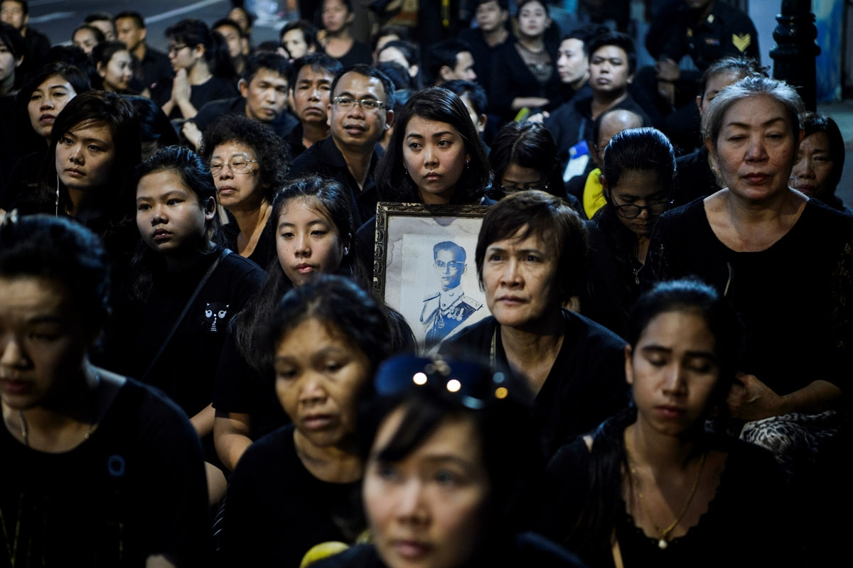 Mourners pray for the late Thai King Bhumibol Adulyadej during the procession transferring the relics and his ashes from the Grand Palace to a local temple in Bangkok on October 29, 2017.