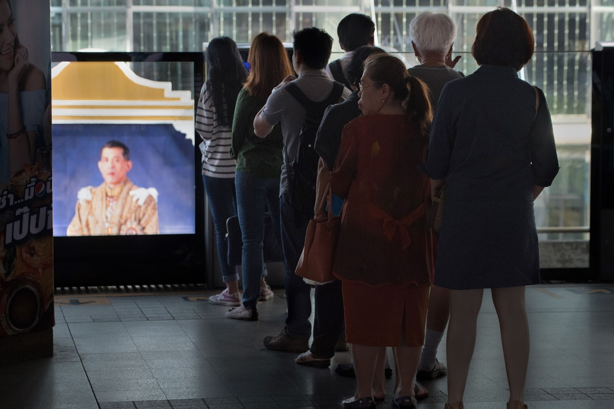 Commuters riding the metro train line up to wait for the next train near a portrait of Thai King Maha Vajiralongkom on October 30, 2017.