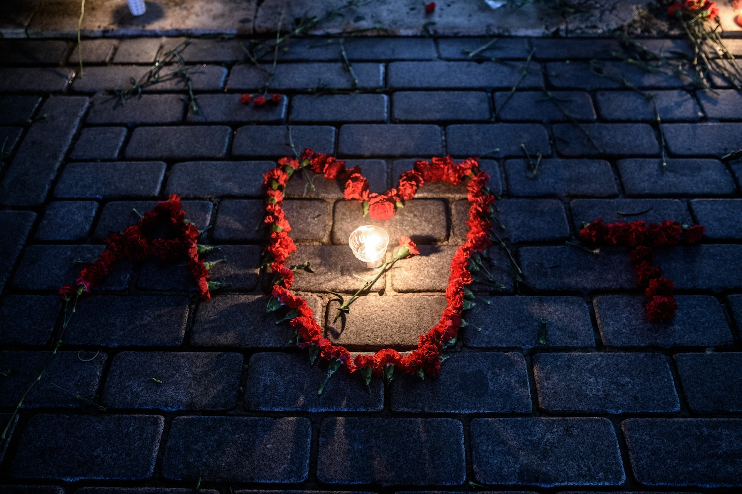 A picture taken on January 13, 2016 shows flowers and candles at a makesgift memorial in tribute to the victims of yesterday deadly attack, on January 13, 2016 on the site of the attack in the Istanbul's tourist hub of Sultanahmet.