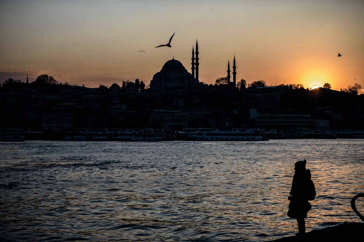 A woman stands on the shore of the Bosphorus river's Golden Horn at Karakoy district as the Suleymaniye Mosque silhouettes against the evening sky, in Istanbul on January 25, 2016.