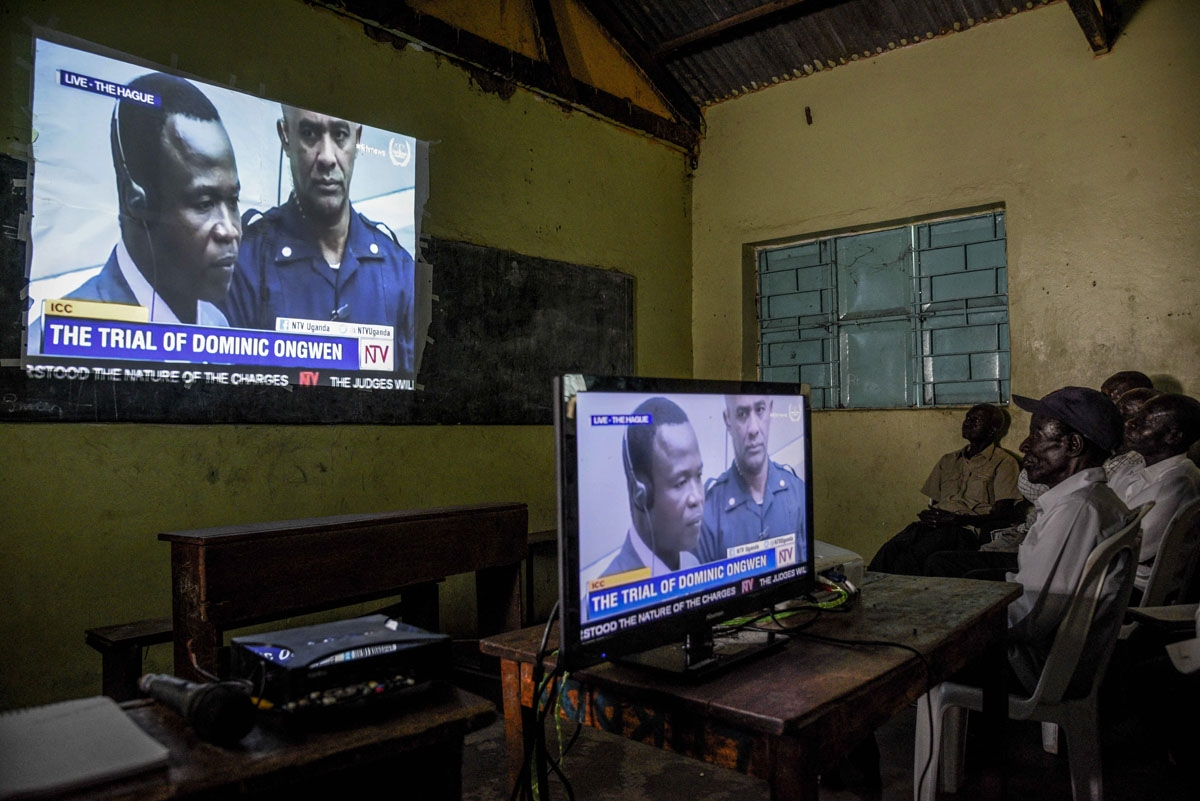 People watch on tv the screening of the start of the ICC (International Criminal Court) trial of former child soldier-turned-warlord Dominic Ongwen in Lukodi, Uganda on December 6, 2016.