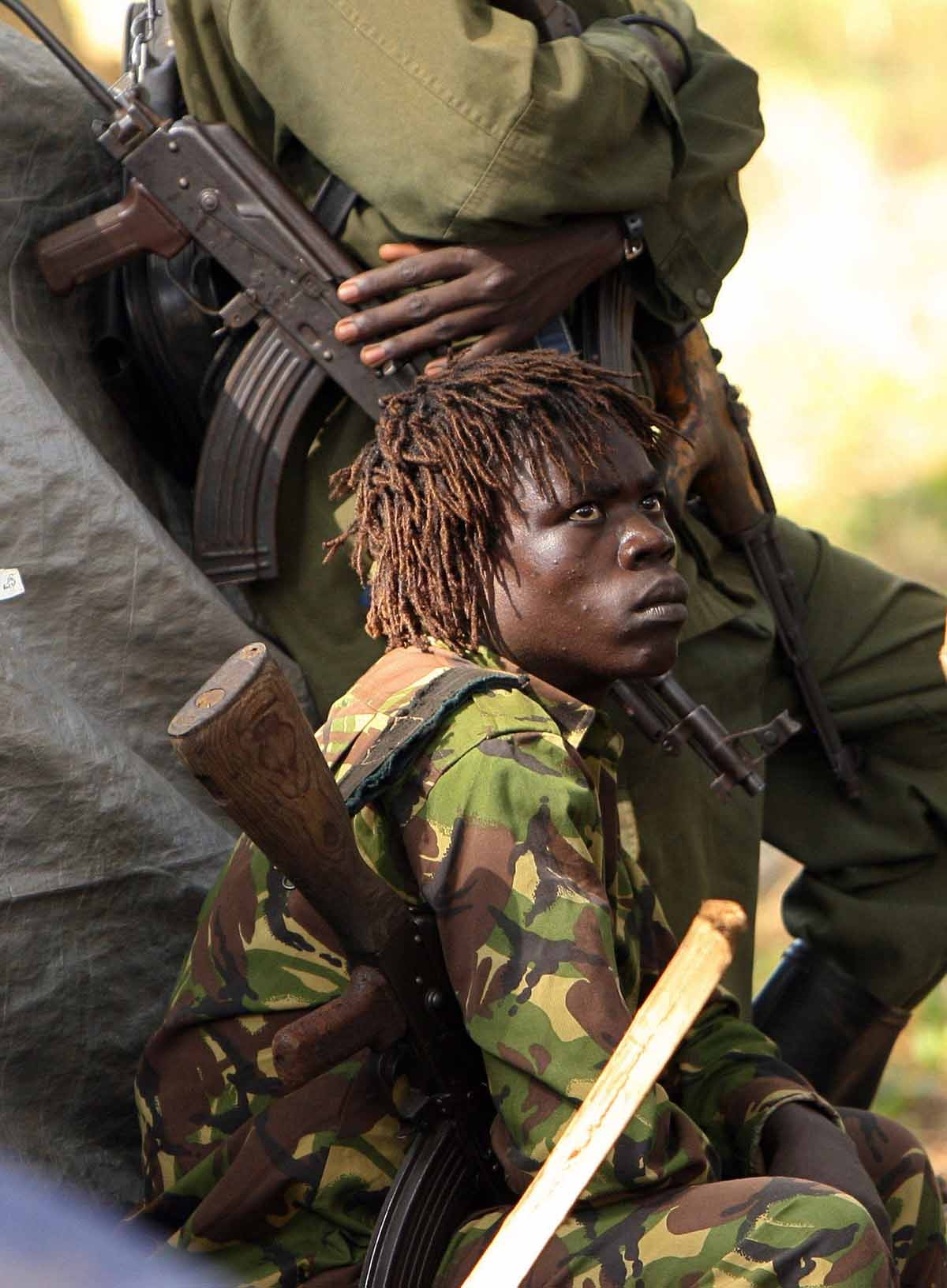 An armed fighter of the Lord's Resistance Army (LRA) looks at a fellow fighter 12 November 2006 during a meeting between the rebel group's leadership and United Nations Emergency Relief coordinator Jan Egeland in Ri-Kwamba, southern Sudan.