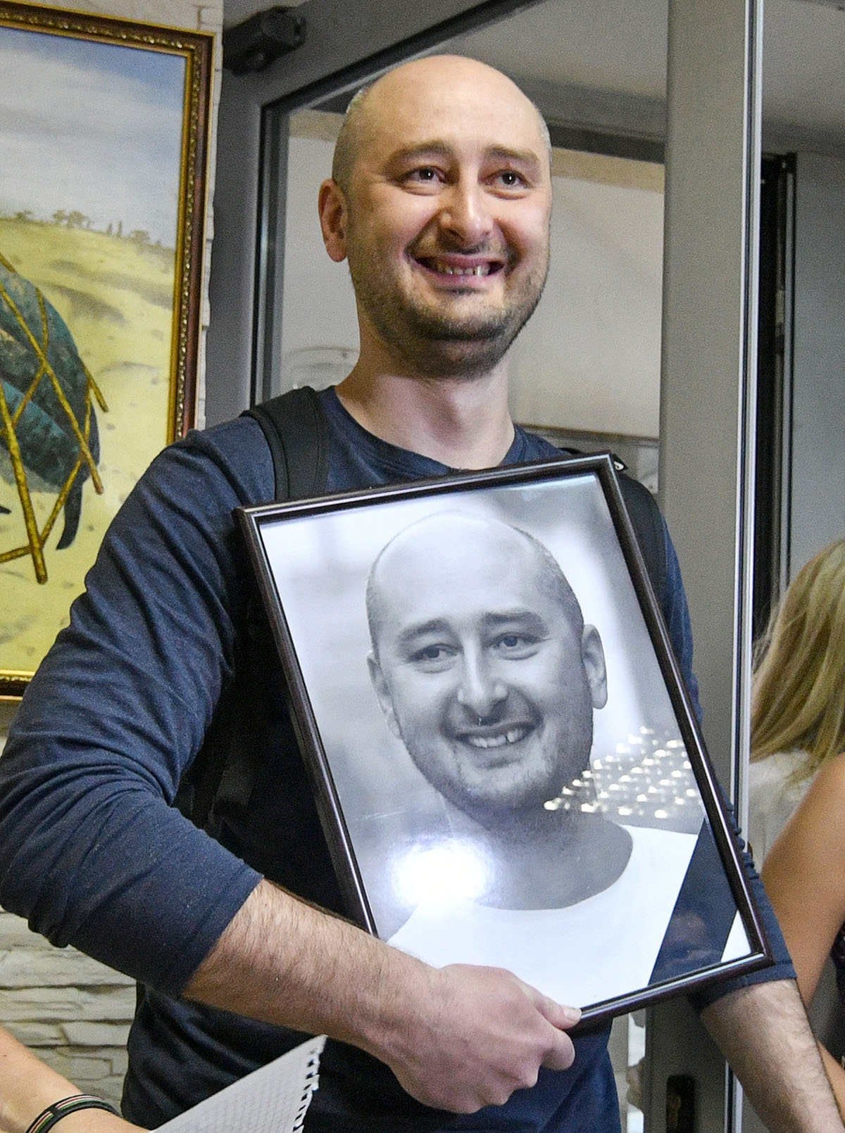 Anti-Kremlin journalist Arkady Babchenko holds a portrait of him that his colleagues displayed in his memory in the offices of his workplace, the ATR TV channel, on May 31, 2018 in Kiev a day following his shock reappearance after Ukrainian authorities s