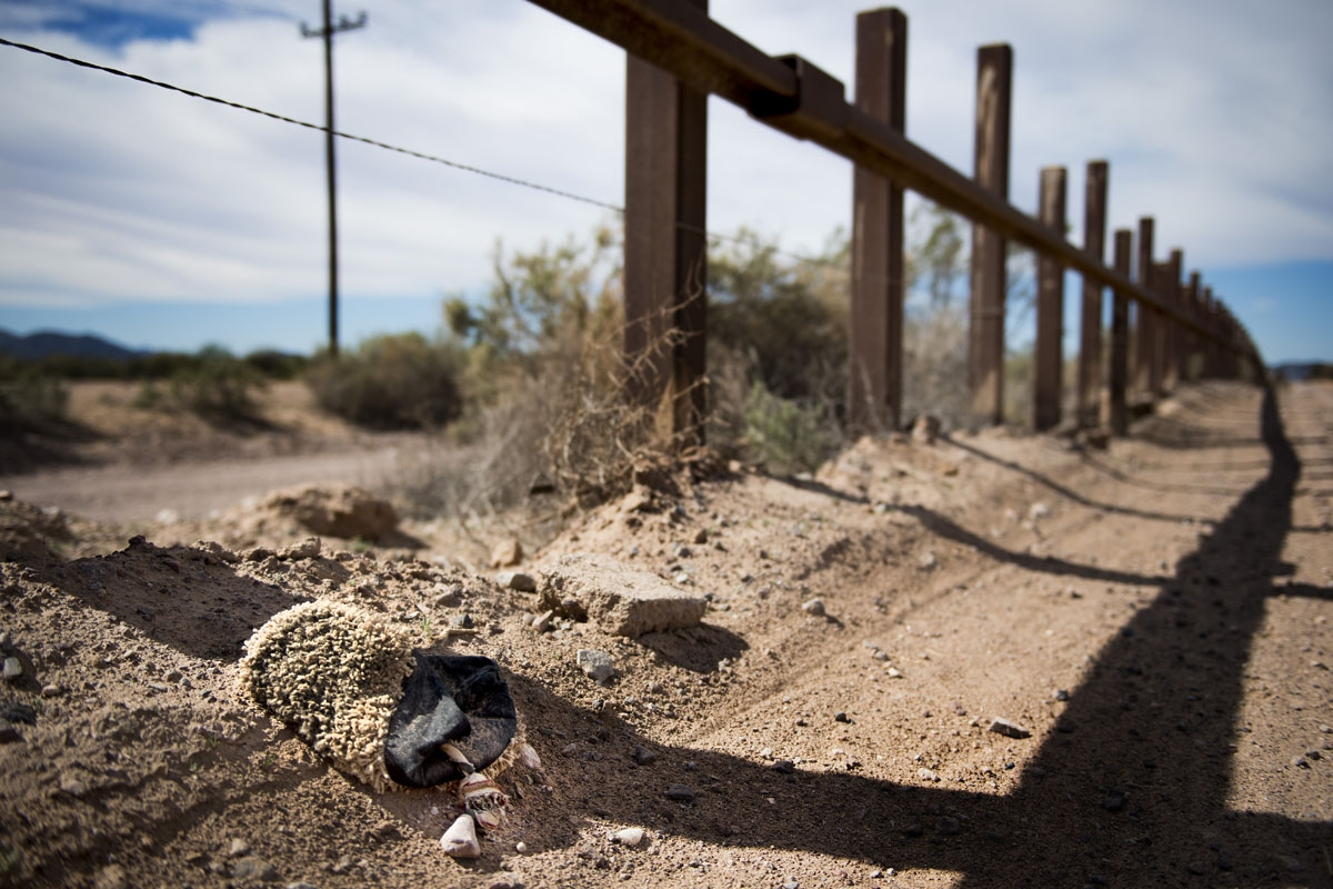 A slipper made of carpet fabric, used to wrap migrants shoes to hide foot tracks, lays next to the border fence outside Lukeville, Arizona, on February 16, 2017, on the US/Mexico border.