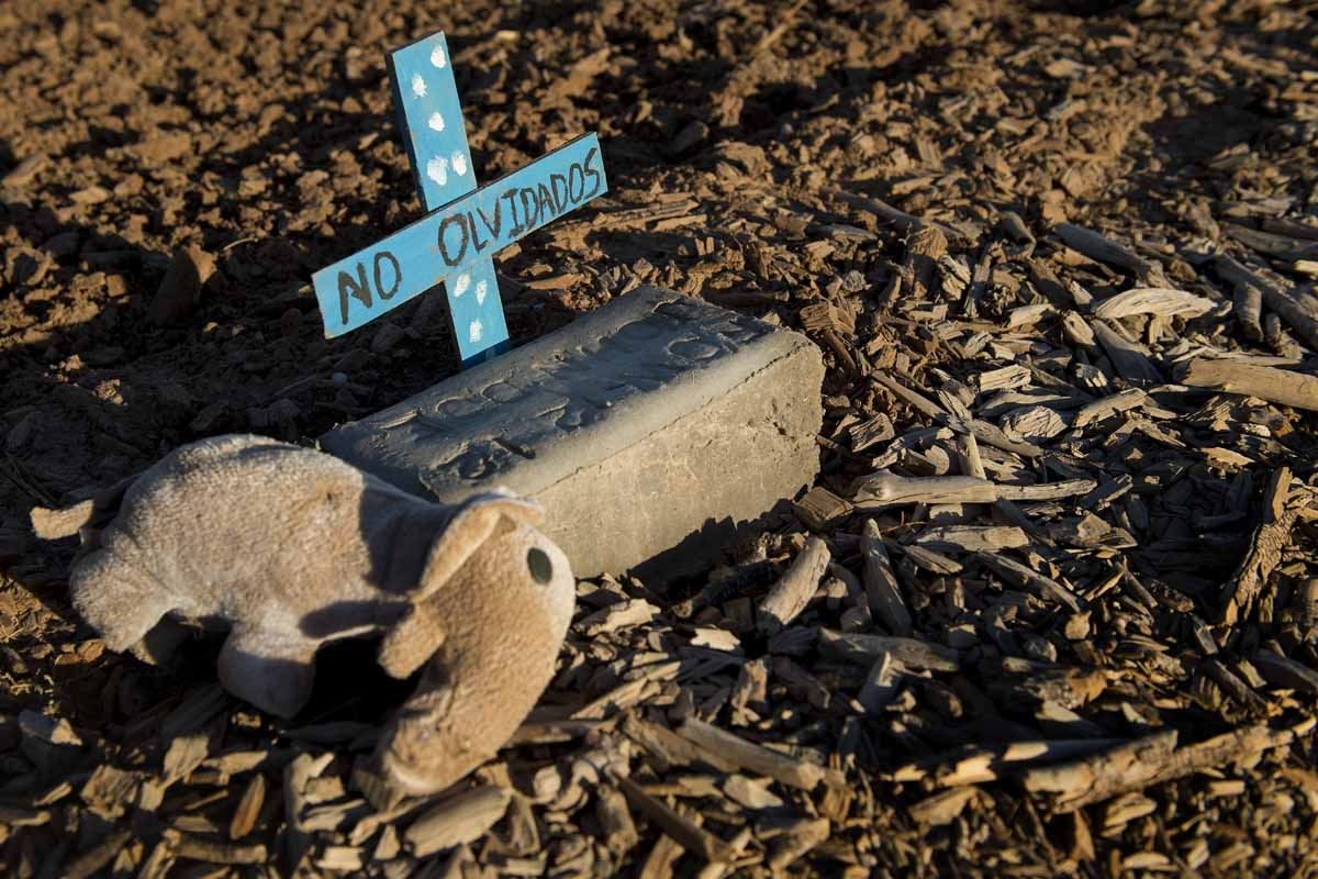 A stuffed animal rests next to a brick inscribed with the words John Doe in an unmarked dirt lot at the end of Terrace Park Cemetery in Holtville, California on February 14, 2017, where the remains of hundreds of unidentified migrants are buried.