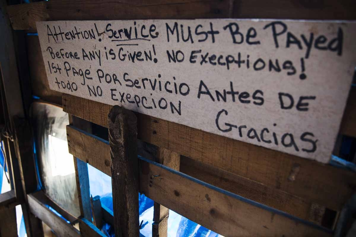 A bi-lingual sign describing terms of service is seen at a heroin encampment in the Kensington neighborhood of Philadelphia, Pennsylvania, on April 10, 2017.