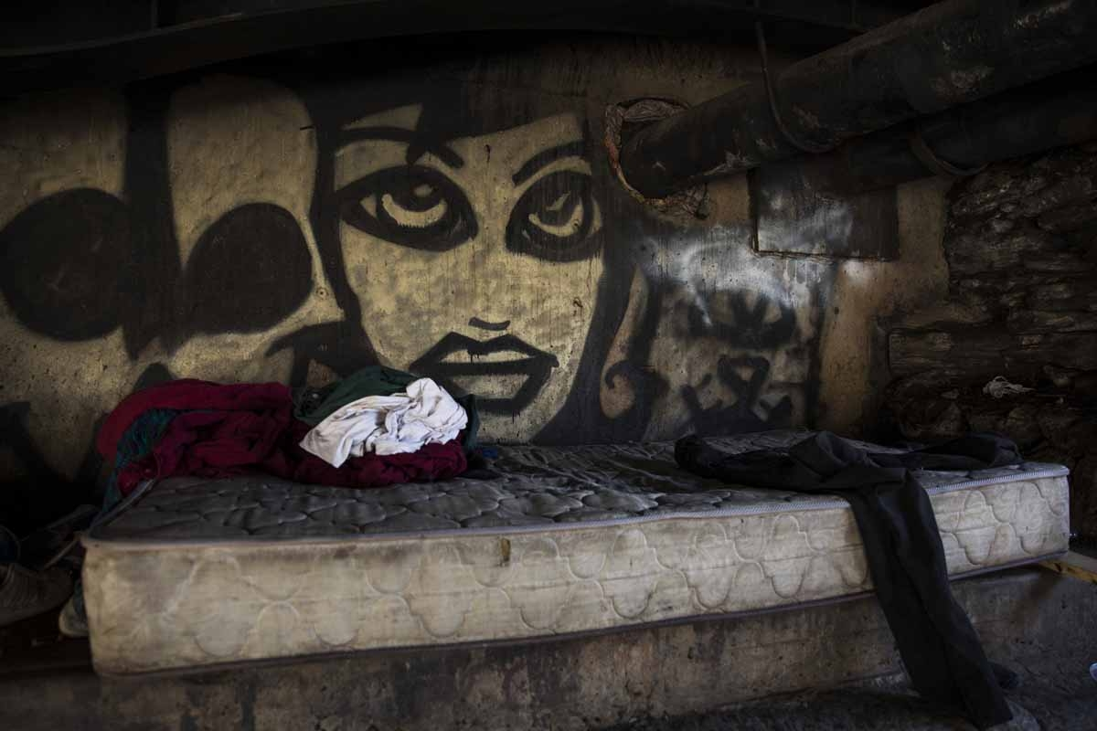 A graffiti portrait looks out from behind a mattress in the Kensington neighborhood of Philadelphia, Pennsylvania, on April 10, 2017