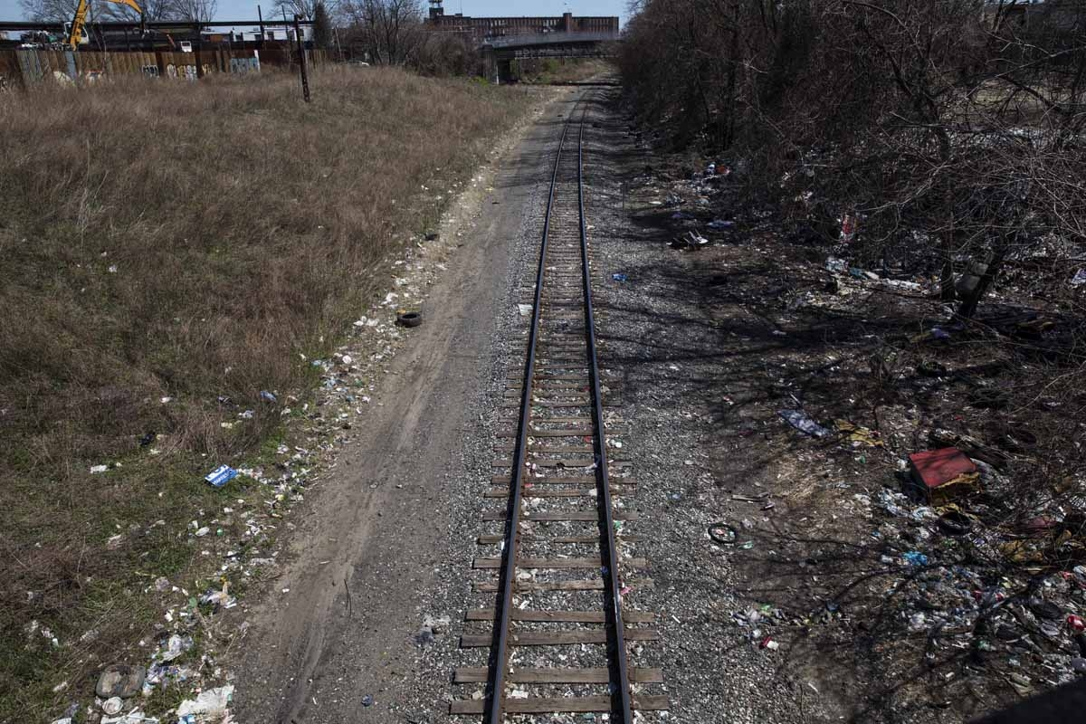 Household trash and empty needle wrapper paper is seen next to rail road tracks near a heroin encampment in the Kensington neighborhood of Philadelphia, Pennsylvania, on April 10, 2017.
