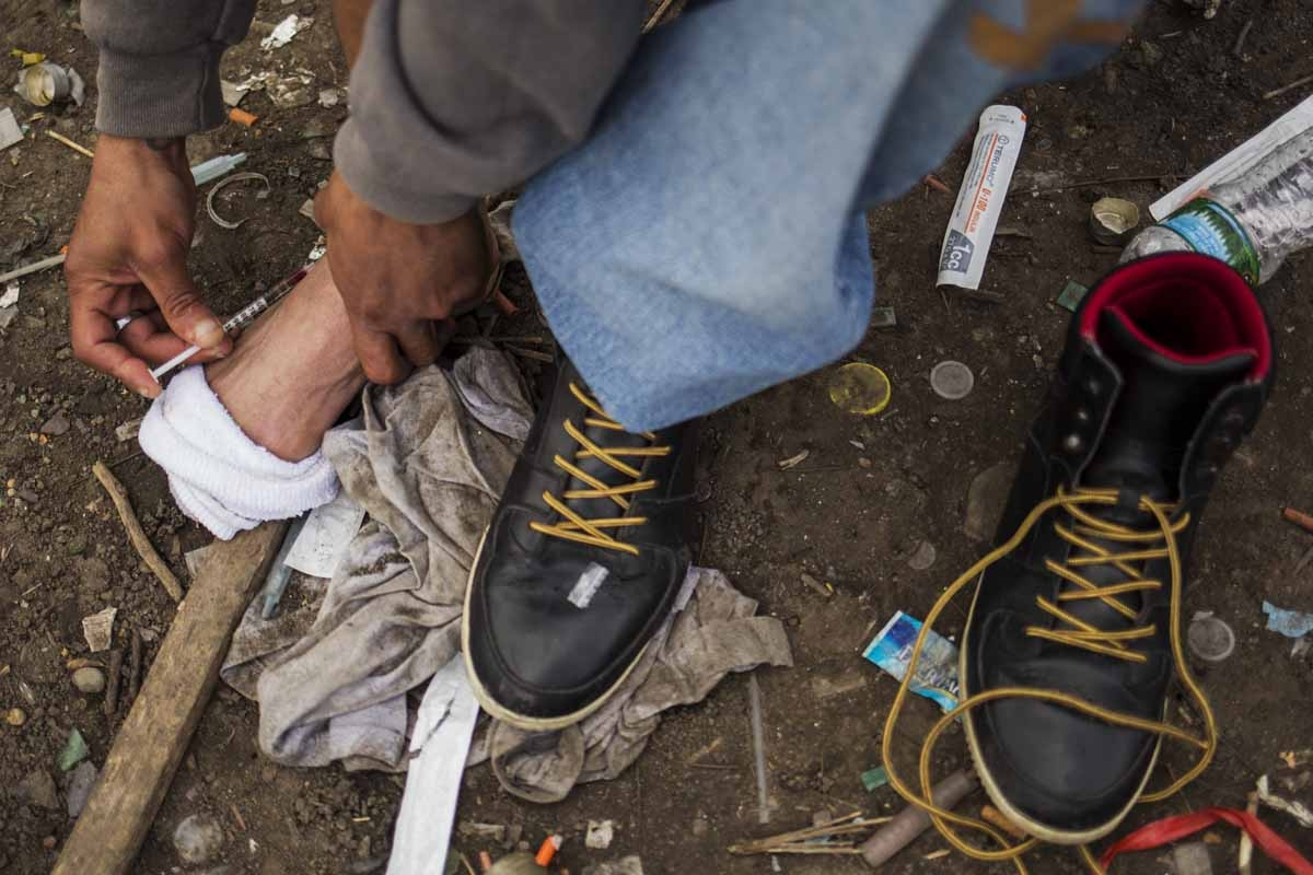 A man injects himself in the foot with heroin near a heroin encampmentin the Kensington neighborhood of Philadelphia, Pennsylvania, on April 14, 2017