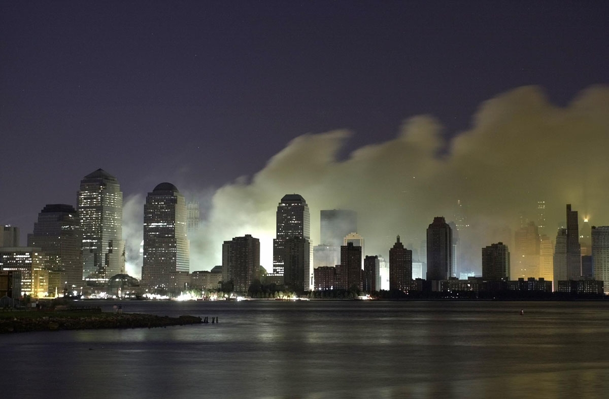 Smoke and ash from the destroyed World Trade Center billows over the southern end of New York City's Manhattan as seen from Jersey City, New Jersey in the early morning, 12 September, 2001