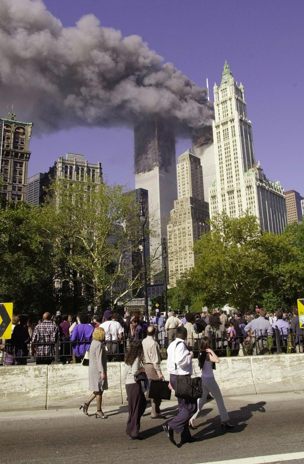 This file photo taken on September 11, 2001 shows pedestrians walking off the Brooklyn Bridge watching as smoke billows from the World Trade Center after two planes crashed into the towers in New York