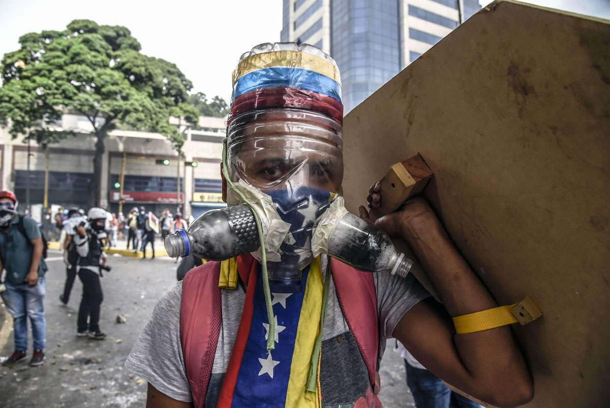 A Venezuelan opposition activist wearing a homemade gas mask takes cover behind a makeshift shield as clashes erupt with riot police during a protest against President Nicolas Maduro, in Caracas on May 8, 2017.