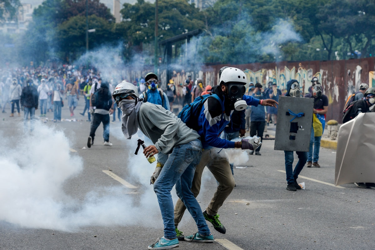 Opposition activists clash with riot police during a protest against President Nicolas Maduro in Caracas on April 26, 2017.  Venezuelan riot police fired tear gas to stop anti-government protesters from marching on central Caracas, the latest clash in a w