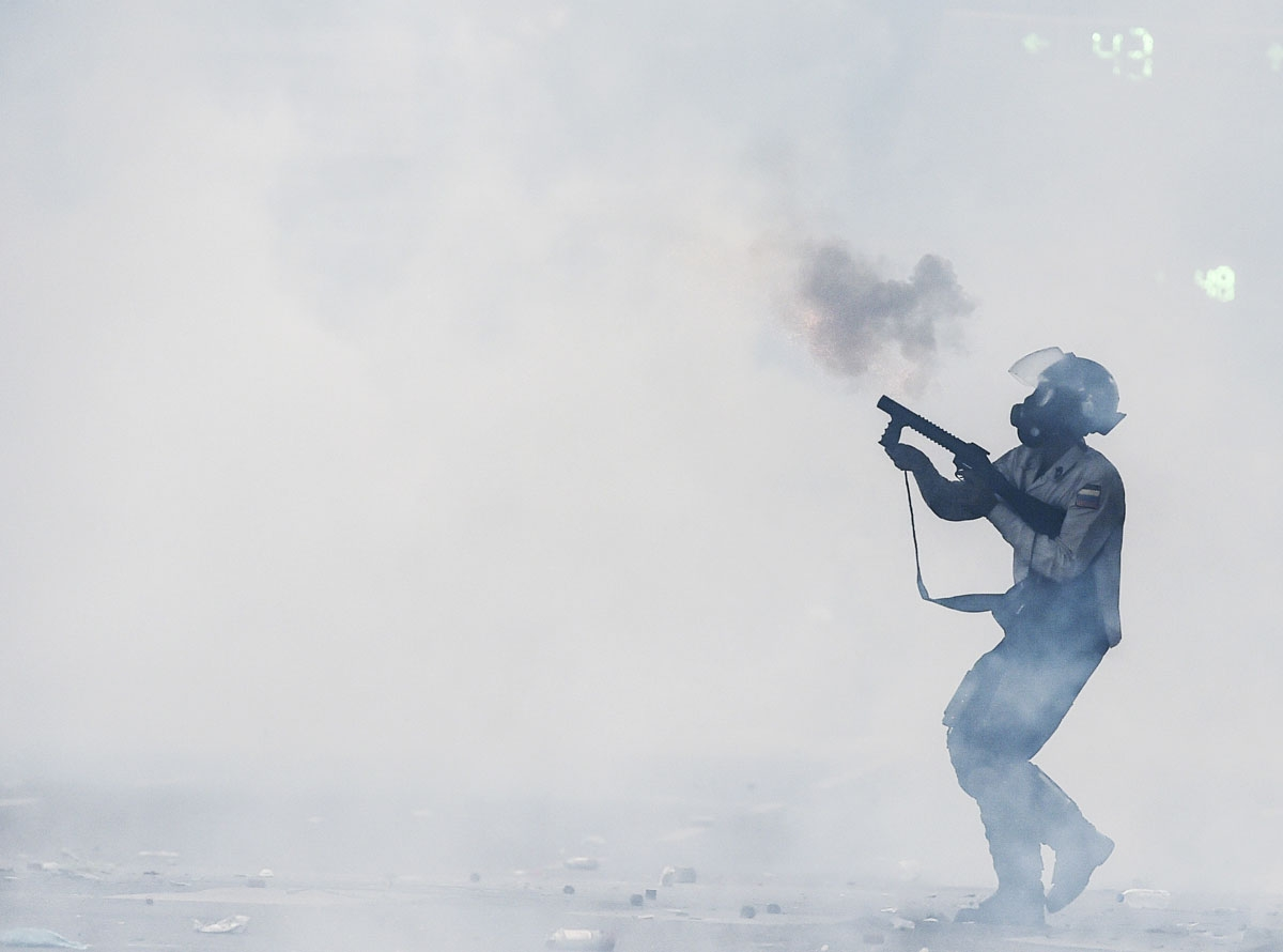 A riot policeman fires a tear gas grenade at opposition activists during a protest against President Nicolas Maduro, in Caracas on May 8, 2017.