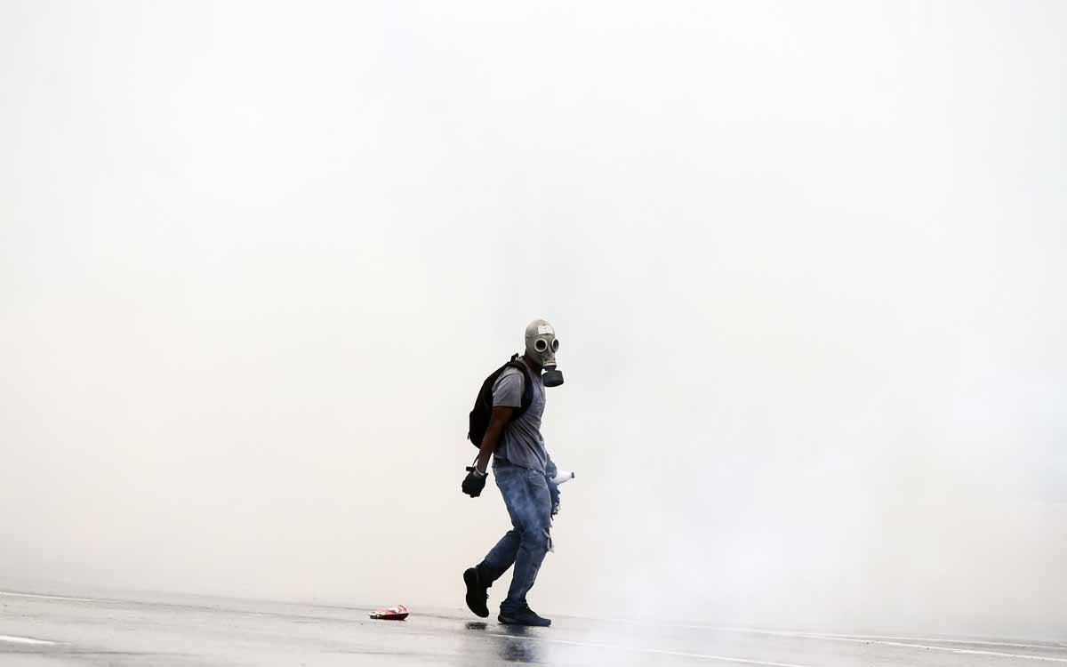 Opposition activists protesting against the government of Nicolas Maduro clash with riot police in Caracas on April 13, 2017. A 32-year-old man died late Thursday after being shot and wounded in a demonstration against President Nicolas Maduro last Tuesda