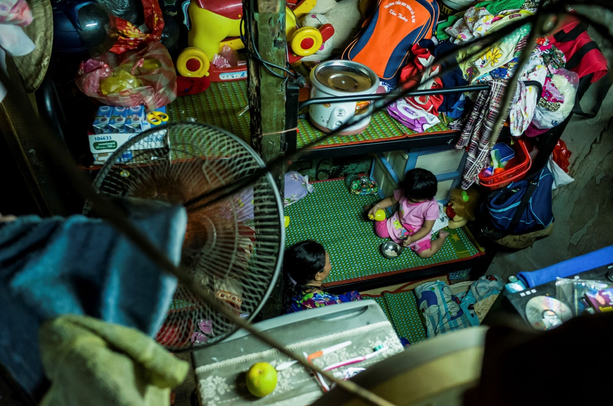 A woman and a child are seen inside one of their relative's two-square-metre home in Ho Chi Minh City on May 2, 2018.