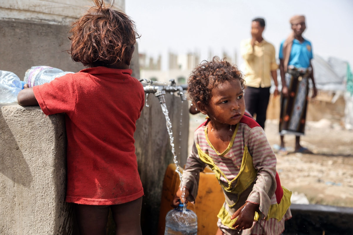 Displaced Yemeni children, who fled fighting between the Saudi-led coalition and Shiite Huthi rebels, fill up carry containers of water from a tap at a camp in the Yemeni coastal city of Hodeidah, on February 17, 2018.