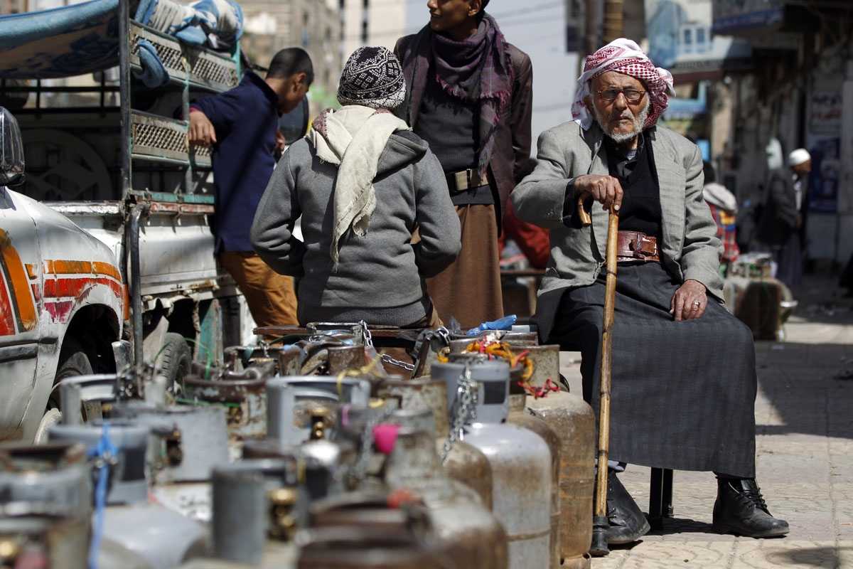Yemenis wait next to empty gas cylinders for gas supplies amid increasing shortages in the Yemeni capital Sanaa, on March 5, 2018