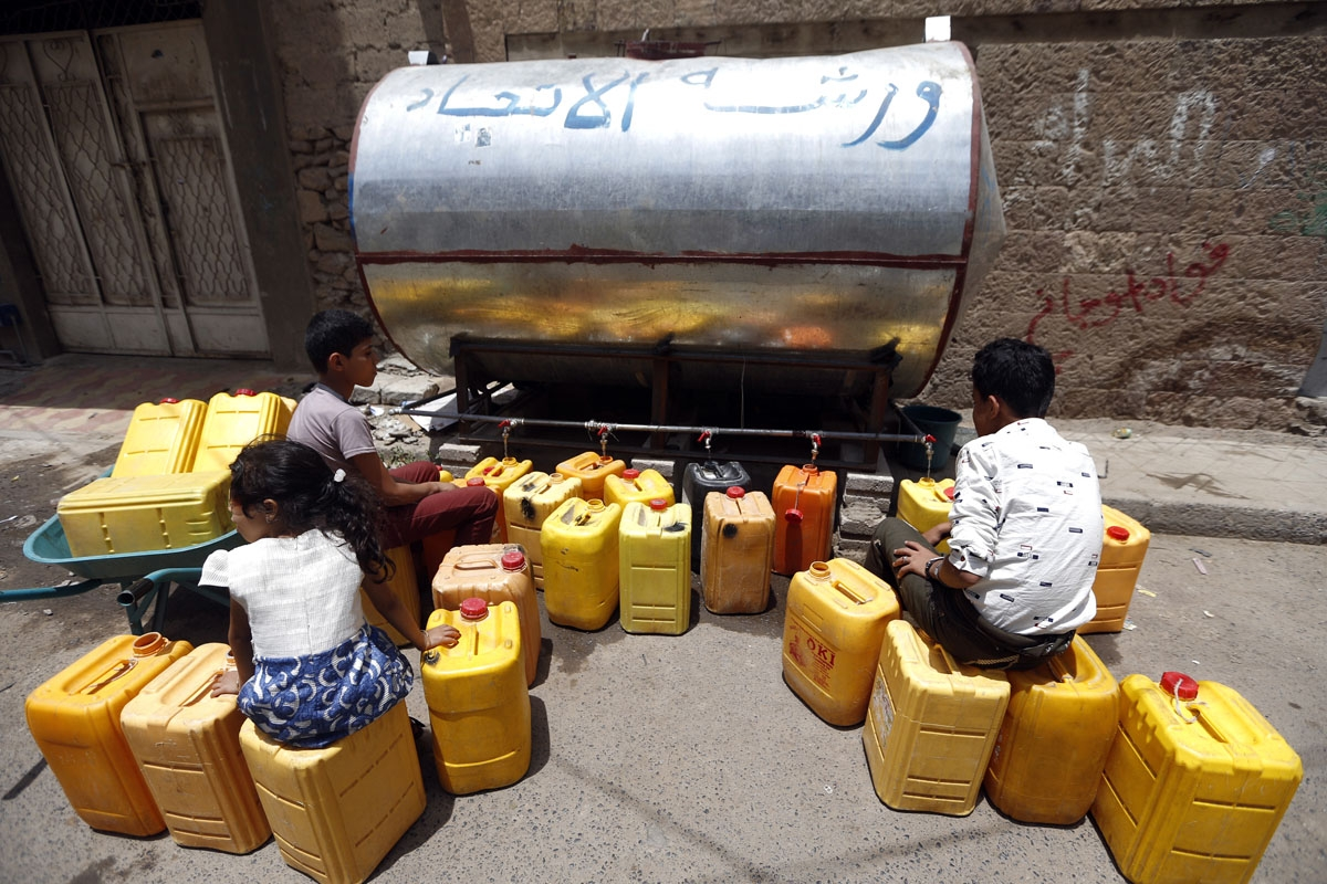 Yemeni children fill jerrycans with safe drinking water from a donated water-tank in the capital Sanaa on July 2, 2017.