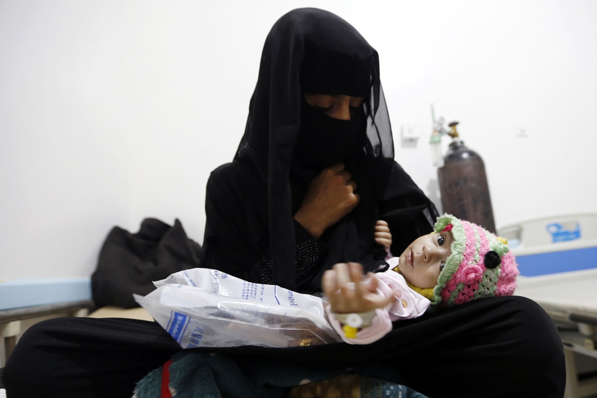 A Yemeni woman holds her child, who is suspected of being infected with cholera, at a makeshift hospital in the capital Sanaa, on August 12, 2017.
