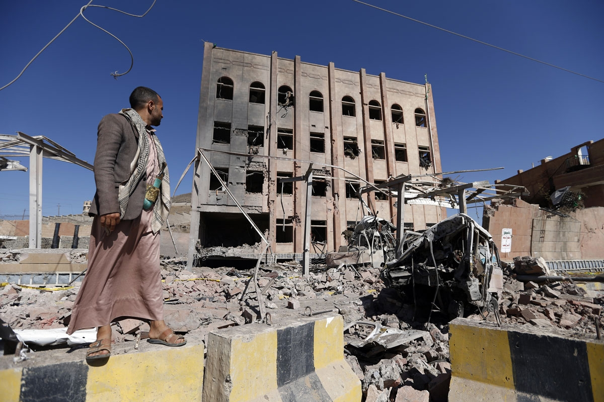 A man stands next to the Yemeni criminal investigations unit in the capital Sanaa on February 5, 2018, a day after the building was hit in an air raid.
