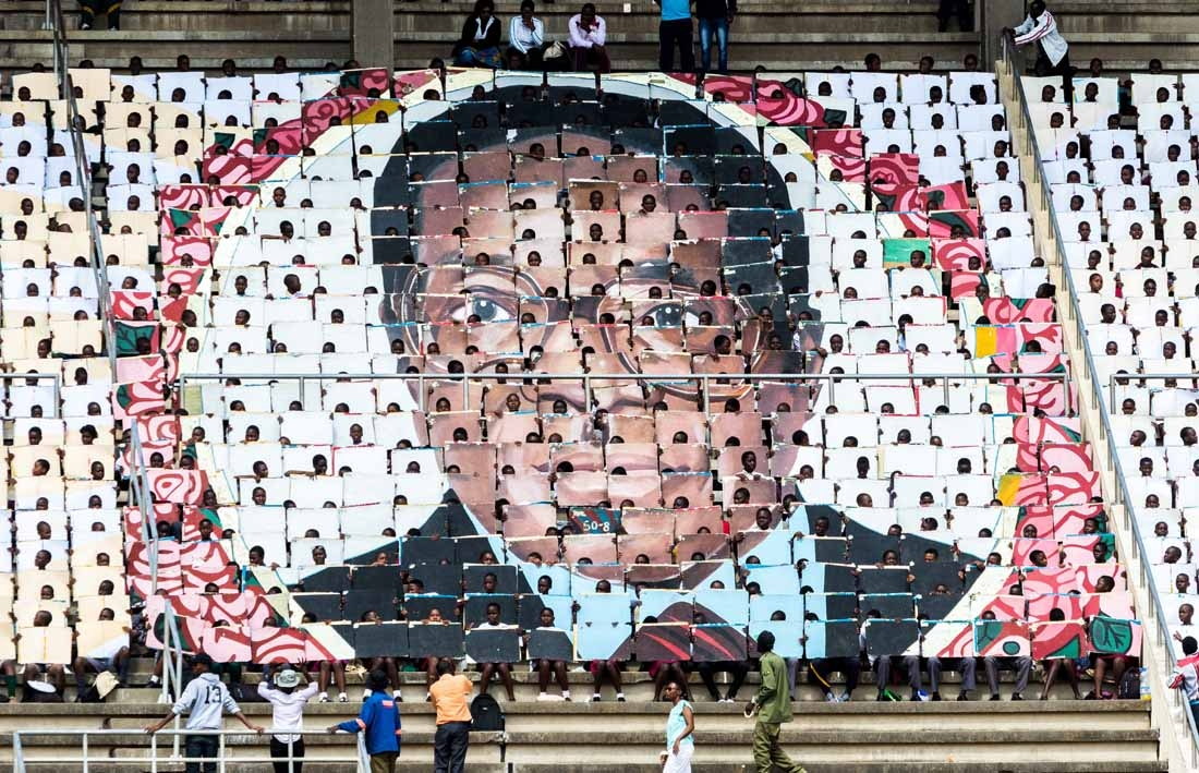 School children hold an image of Zimbabwe's President Robert Mugabe during the country's 37th Independence Day celebrations at the National Sports Stadium in Harare April 18, 2017.