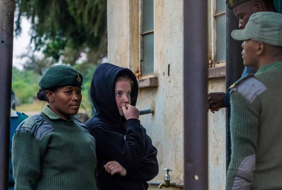 US journalist Martha O'Donovan (C), who was arrested on charges of insulting Zimbabwe's president and attempting to subvert the country's regime, talks with Zimbabwe Correctional Services officers as she leaves Chikurubi Maximum Prison near Harare, after