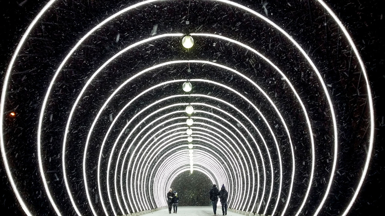 People walk under the major snowfall in central Moscow on January 8, 2018.
