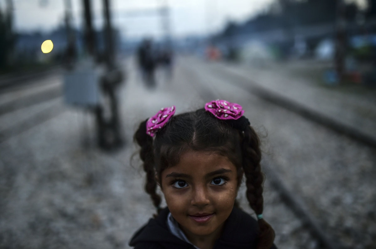 A Syrian refugee girl stands on the rail way at the makeshift camp along the Greek-Macedonian border, near the Greek village of Idomeni on April 1, 2016, where thousands of refugees and migrants are stranded by the Balkan border blockade.