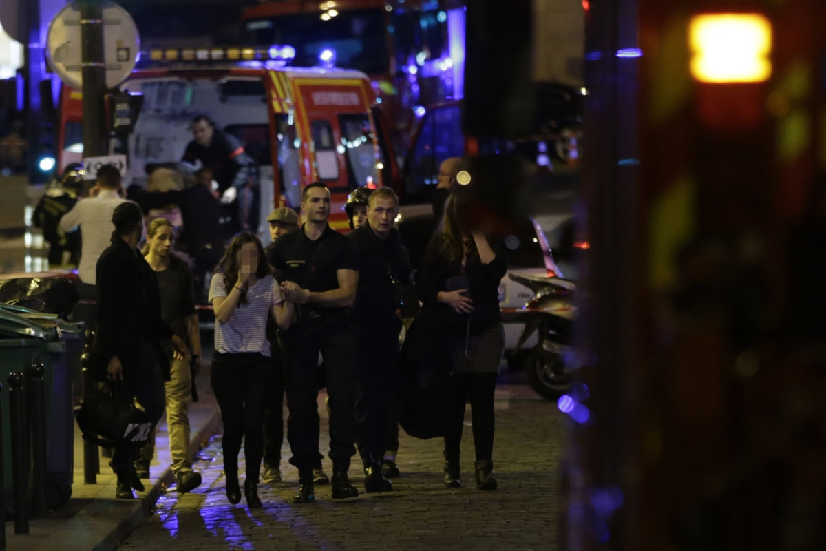 People are evacuated following an attack at the Bataclan concert venue in Paris, on November 13, 2015. At least 18 people were killed in multiple attacks in Paris Friday,