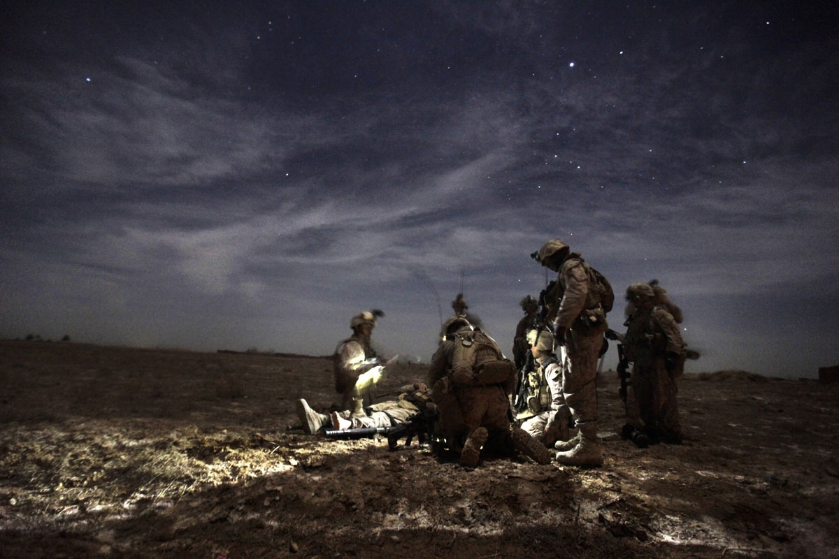 US Marines with 1/3 Charlie Company treat Lance Corporal Kris Mottley (21) from Pensylvania as they wait for a MEDEVAC helicopter, after their MRAP vehicle was hit by an Improvised Explosive Device (IED) in Trikh Nawar on the north-eastern outskirts of Ma