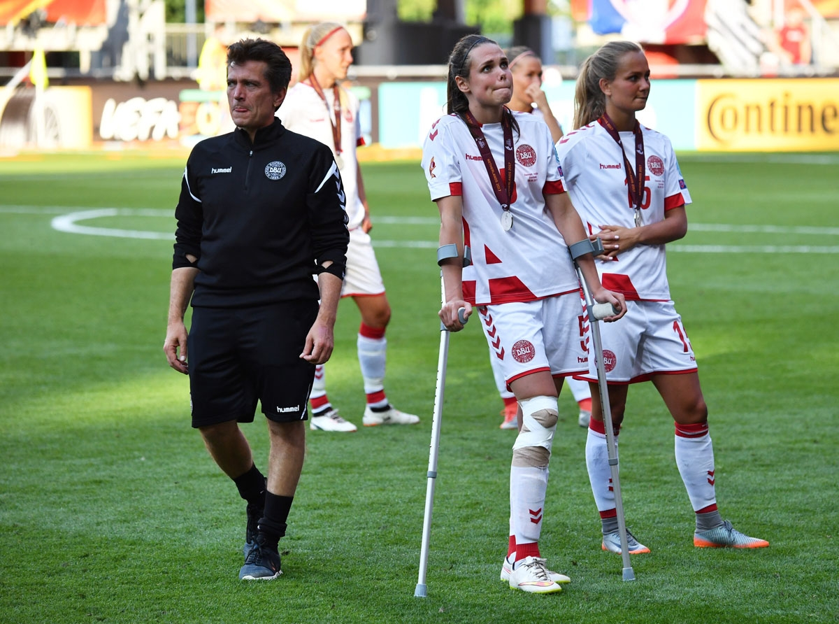 Denmark's head coach Nils Nielsen (L) and his team players react at the end of the UEFA Women's Euro 2017 football tournament final match between Netherlands and Denmark at Fc Twente Stadium in Enschede on August 6, 2017