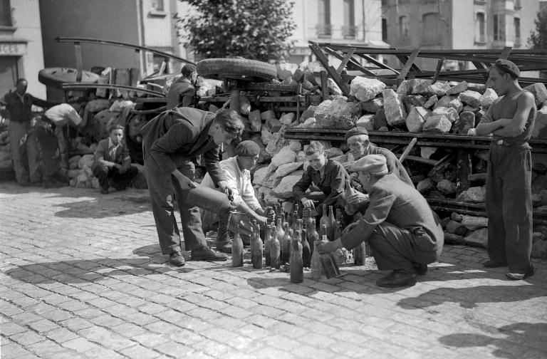 Des combattants FFI confectionnent des bouteilles incendiaires derrière une barricade