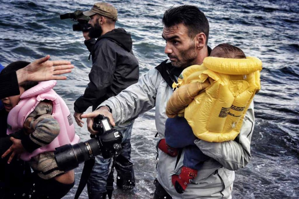 Aris Messinis transporte un enfant sur le rivage à Lesbos. (Photo