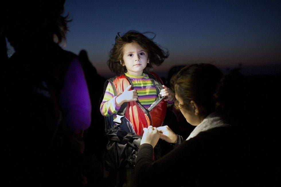 Une enfant se fait retirer son gilet de sauvetage à son arrivée à Kos, le 13 août 2015 (AFP / Angelos Tzortzinis)