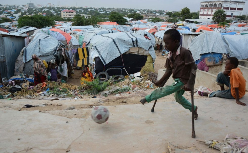 Un enfant atteint de la polio joue au football dans le camp de personnes déplacées de Sayyid à Mogadiscio, le 12 juin 2014 (AFP Photo / Mohamed Abdiwahab)
