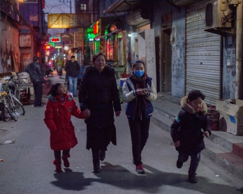 This picture taken on February 16, 2017 shows people walking on a street in the Heiqiaocun migrant village in Beijing.