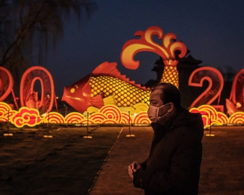 A man wears a protective facemask to help stop the spread of a deadly SARS-like virus which originated in the central city of Wuhan, as he walks on the outskirts of the Forbidden City and a New Year instalation displaying a fish and the number 2020 in Bei