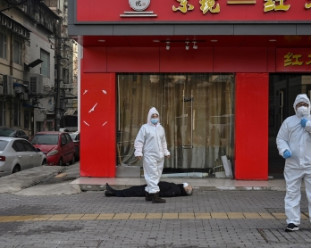 EDITORS NOTE: Graphic content / This photo taken on January 30, 2020 shows officials in protective suits checking on an elderly man wearing a facemask who collapsed and died on a street near a hospital in Wuhan. - AFP journalists saw the body on January 3