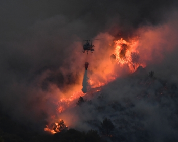 An helicopter carries an extinguisher in the struggle against a fire that spread near Vitrolles, southern France on August 10, 2016