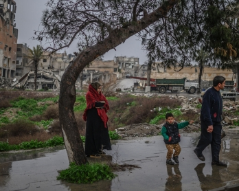 A couple and their child wait to cross a street in the northern Syrian city of Raqa on February 14, 2019. - In 2014, jihadists of the Islamic State (IS) seized the city of Raqa from Syrian rebels.