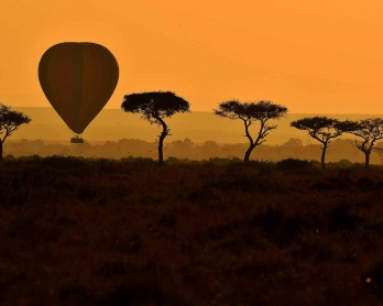 A hot air balloon carrying tourists is pictured during the annual wildebeest migration in the Masai Mara game reserve on September 14, 2016.  / AFP PHOTO / CARL DE SOUZA