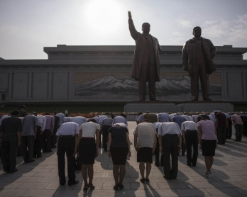 People bow as they pay their respects to the statues of former North Korean leaders Kim Il-Sung and Kim Jong-Il, at Mansu hill in Pyongyang on July 7, 2016