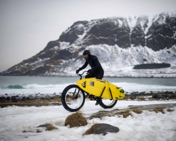 Australian surf legend from the 80's Tom Carroll, 55, rides a bike in Unstad on March 9, 2017 before surfing the Arctic waves of the Atlantic Ocean. / AFP PHOTO / OLIVIER MORIN