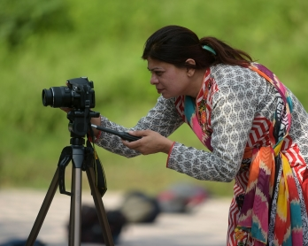 In this photograph taken on August 30, 2016,  Shazia Bhatti, a Pakistani 38-year old journalist shoots video footage during an assignment in Islamabad. / AFP PHOTO / AAMIR QURESHI