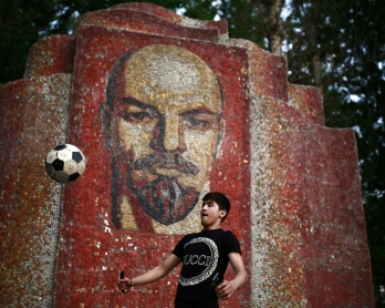 A boy juggles with a ball in front of a mosaic depicting Russian communist leader Vladimir Lenin, on June 26, 2018 in Kazan during the Russia 2018 World Cup football tournament.